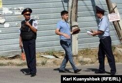 Полицейские на месте антитеррористической спецоперации 17 августа 2012 года в поселке Баганашыл Алматинской области.