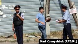 """""""Терроризмге қатысы болуы мүмкін 5 күдікті жойылған"""" оқиға орнында жүрген полицейлер. Алматы облысы, Қарасай ауданы, 17 тамыз 2012 жыл."""