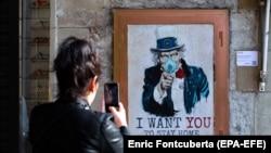 Девушка снимает на смартфон плакат художника TVBoy, на котором Дядя Сэм рекомендует каждому оставаться дома. Барселона, 13 марта 2020 года.