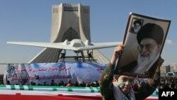 İran - ali dini liderin potretini tutmuş uşaq ələ keçirilən pilotsuz ABŞ təyyarəsi önündə.
