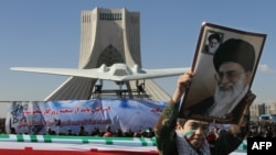 An Iranian boy holds a portrait of Supreme Leader Ayatollah Ali Khamenei as he walks past a replica of a captured U.S. drone and anti-Israeli banners on display near the Azadi (Freedom) tower on the 33rd anniversary of the Islamic Revolution.