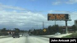 Напис над шосе у долині Сан-Фернандо в Лос-Анджелесі: «Мийте руки, будьте здорові, уникайте COVID-19», 15 березня 2020 року