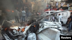 A destroyed car is seen at the site of an explosion in Beirut's southern suburbs on August 15.