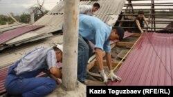 Гражданские активисты ремонтируют кровлю барачного дома, где живет семья диссидента Арона Атабека. Алматы, 29 сентября 2012 года.