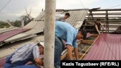 Гражданские активисты ремонтируют кровлю барачного дома, где живет семья Арона Атабека. Алматы, 29 сентября 2012 года.