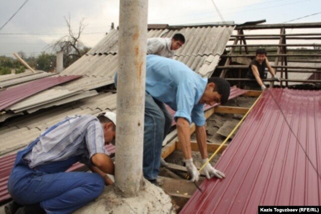 Civil society activists perform repairs on Atabek's home in September 2012.