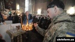 Військовослужбовець ставить свічку під час Різдвяного богослужіння в соборі святого Івана Богослова, Харків, 7 січня 2016 року