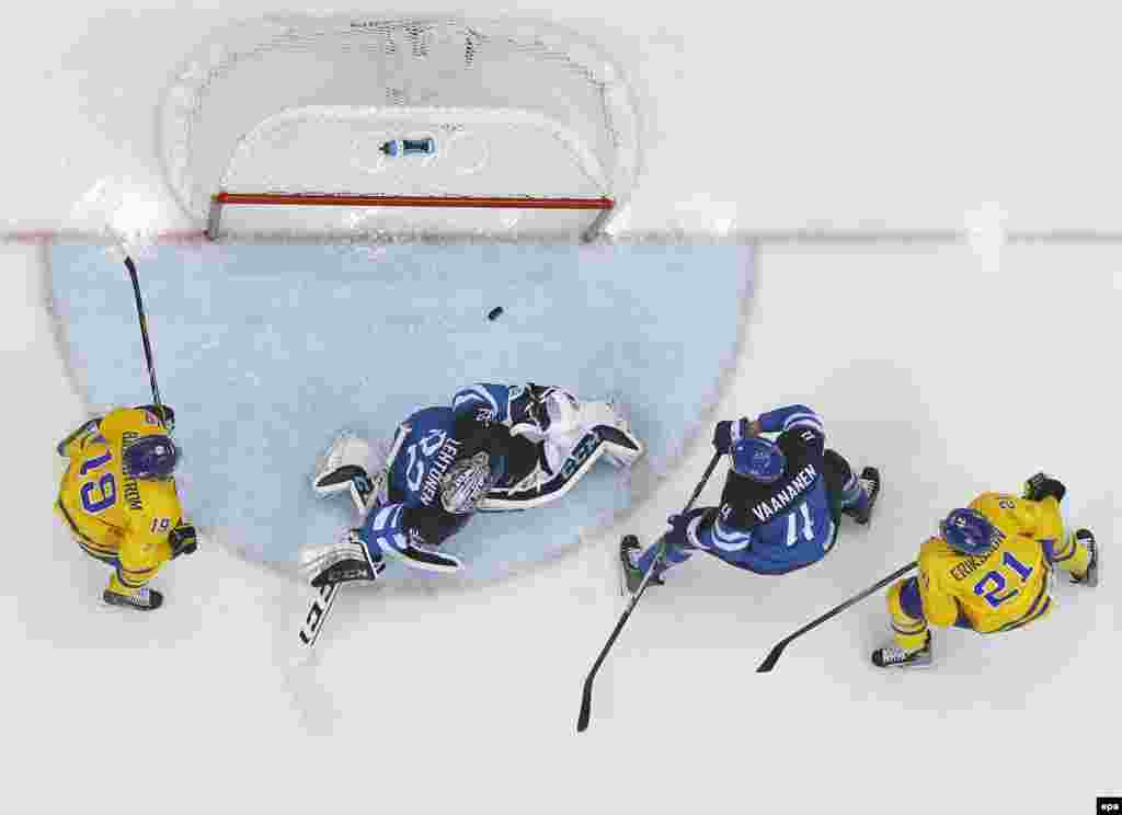 Sweden's Loui Eriksson (left) and Nicklas Backstrom and Finland's Ossi Vaananen and goalie Karl Lehtonen watch the puck going over the bar during the semifinal between Sweden and Finland. (epa/Larry W. Smith)