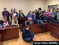 Әлімжан Ізбасаров өзіне қозғалған іске наразылық ретінде сот залында жерге отырып алған. Нұр-Сұлтан, 4 мамыр 2019 жыл.