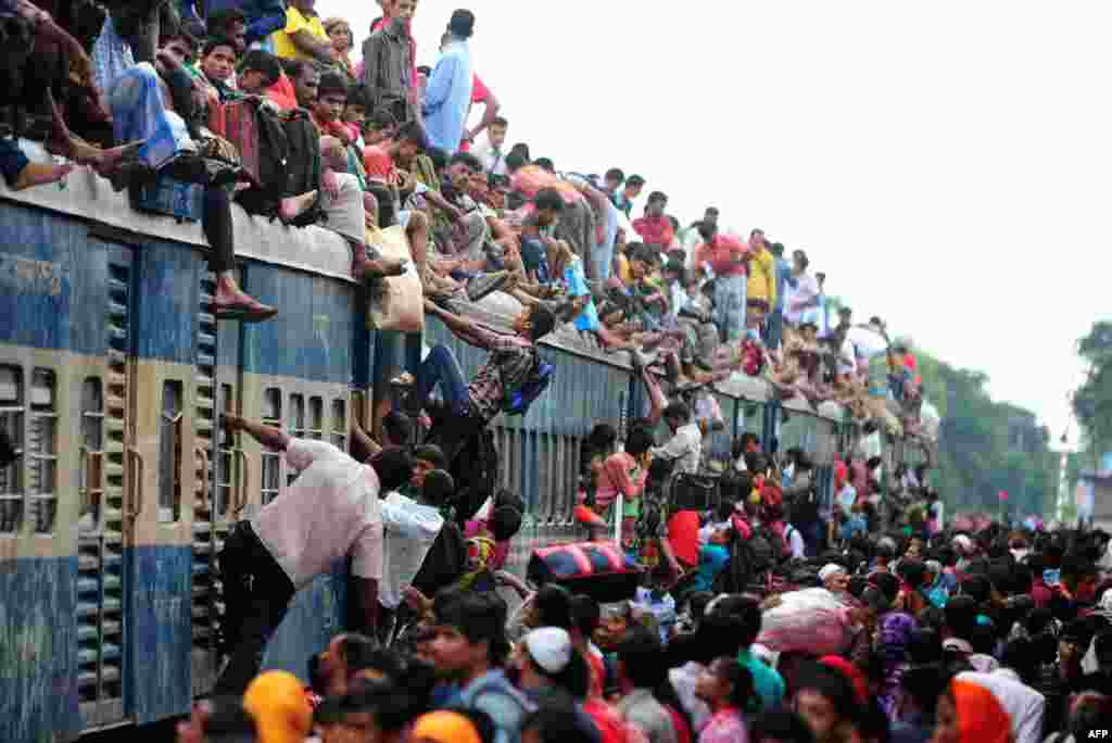 Bangladeshis cram onto a train in Dhaka as they rush home to their respective villages to be with their families ahead of the Muslim festival of Eid al-Fitr. (AFP/Munir uz Zaman)