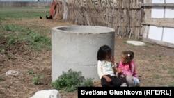 Ауру лақтың қасында ойнап отырған балалар. Қостанай облысы Қабырға ауылы, 8 маусым 2015 жыл.
