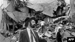 A man walks over the rubble left after a bomb exploded at the Argentinian Israelite Mutual Association (AMIA) in Buenos Aires, 18 July 1994