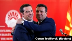 Greek Prime Minister Alexis Tsipras (left) and North Macedonian Prime Minister Zoran Zaev hug as they attend a news conference in Skopje on April 2.