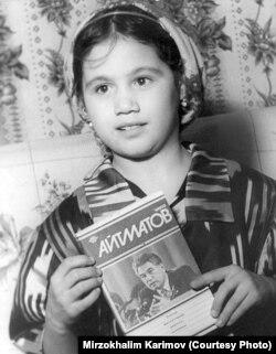 Тажик кызы Жамила Айтматовдун китебин кармап турат.