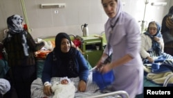 A midwife helps a mother with her newborn baby at the Razai Foundation Maternity Hospital in Herat. In Afghanistan, not having a son can doom a mother's marriage.