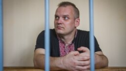 Dzmitry Halko sits in his cage in a Minsk court on July 17, 2018.