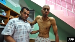Cuban opposition activist Guillermo Farinas (right) stands with the help of a doctor at his home in Santa Clara, Cuba, in March.