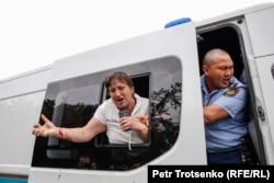 Повредившая руку женщина выглядывает из полицейского автомобиля во время массовых задержаний в Алматы. 10 июня 2019 года.