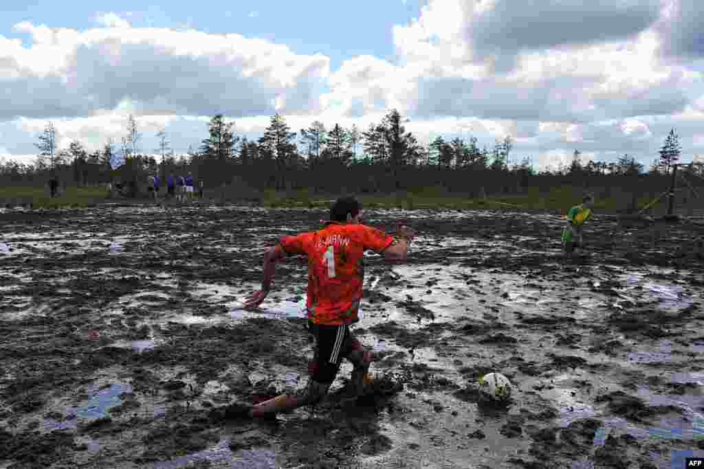 A Russian swamp-football player kicks the ball during the Russian Swamp Football Cup outside of St. Petersburg. (AFP)