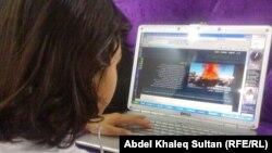 شابة عراقية تتصفّح مواقع ألكترونية