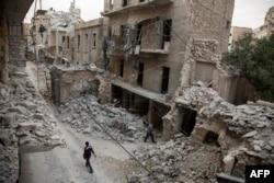دو مرد سوری در منطقهای از حلب که هدف حملات هوایی ارتش بشار اسد قرار گرفتهاست