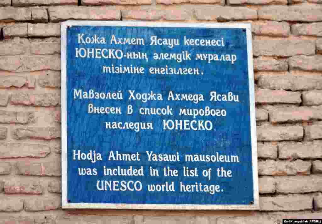 Табличка на здании мавзолея Ходжа Ахмета Яссауи. Туркестан, 21 августа 2012 года.