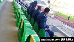 Polisiýa işgärleri futbola tomaşa edýärler.