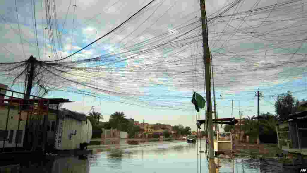Tangled electrical wires are seen over a rain-flooded street in the Iraqi capital, Baghdad. (AFP/Sabah Arar)
