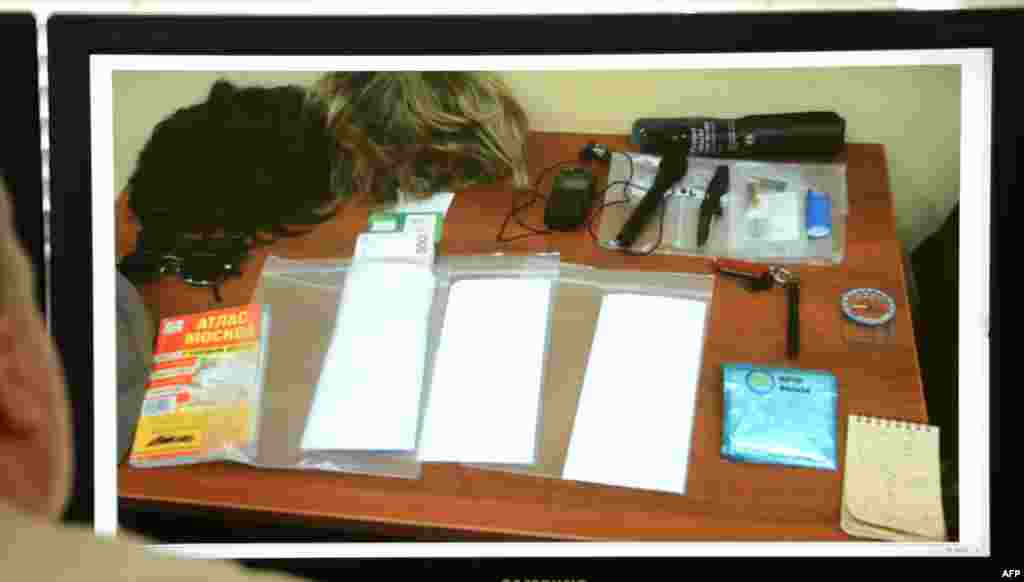 A man looks at a computer screen displaying belongings described as being owned by Ryan C. Fogle in a photo released by the Russian Federal Security Service. The items included two wigs, a compass, a Moscow map, a small knife, and stacks of euro banknotes.