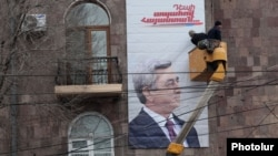 Armenia - Workers put up an election billboard of President Serzh Sarkisian in Yerevan, 21Jan2013.