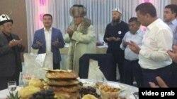 Скриншот из видео, где мэр Оша Айтмамат Кадырбаев дарит национальную одежду ичик кандидату в президенты Сооронбаю Жээнбекову.