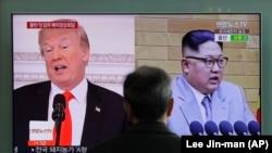 Мужчина на железнодорожном вокзале в Сеуле смотрит телевизор, на экране которого - изображения президента США Дональда Трампа и северокорейского лидера Ким Чен Ына. 27 марта 2018 года.
