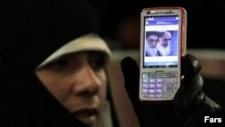 Иранская женщина держит в руках мобильный телефон, на экране которого изображен верховный лидер Ирана Хаменеи и основатель Исламской Республики Иран Хомейни. Протест оппозиции в Тегеране. Декабрь 2009 года.