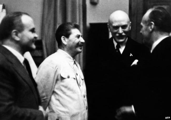 Йосиф Сталін (другий ліворуч), міністр закордонних справ СРСР В'ячеслав Молотов (ліворуч) та міністр закордонних справ нацистської Німеччини Йоахім фон Ріббентроп (крайній праворуч) під час укладання Пакту Молотова-Ріббентропа. Москва, 23 серпня 1939 року