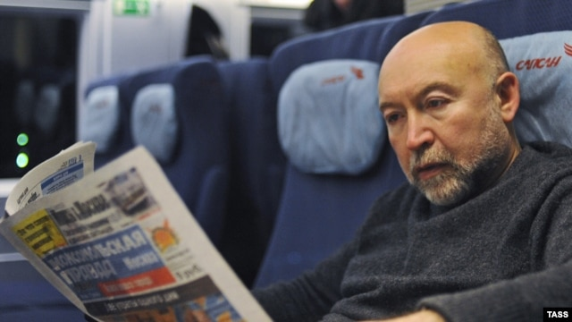 Russia -- A passenger reads a newspaper in train, Moscow, 18Dec2009