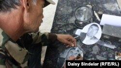 Этнический узбек Рашид работает над надгробной плитой. Ош, 12 июня 2011 года.