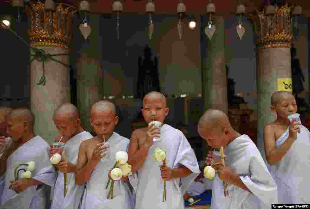Newly ordained Buddhist monks sip water during a mass Buddhist monk ordination ceremony for hill tribesmen at Wat Benchamabophit, also known as the Marble Temple, in Bangkok. (epa-EFE/Rungroj Yongrit)