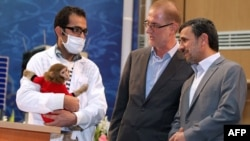 Президент Ахмадинежад (справа) смотрит на обезьянку-космонавта (слева)