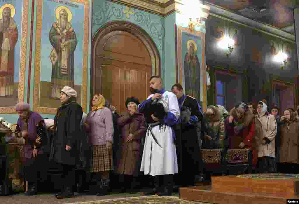 In Russia, Orthodox believers attend a service on the eve of Orthodox Christmas in Kazan Cathedral in Volgograd.