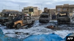 A picture taken with a mobile phone shows burnt vehicles at the scene of a blast from a massive car bomb, which killed scores of people in Baghdad on February 16.