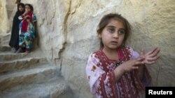 Девочки стоят у стены в небольшом селе неподалеку от портового города Чехбехар в Иране.