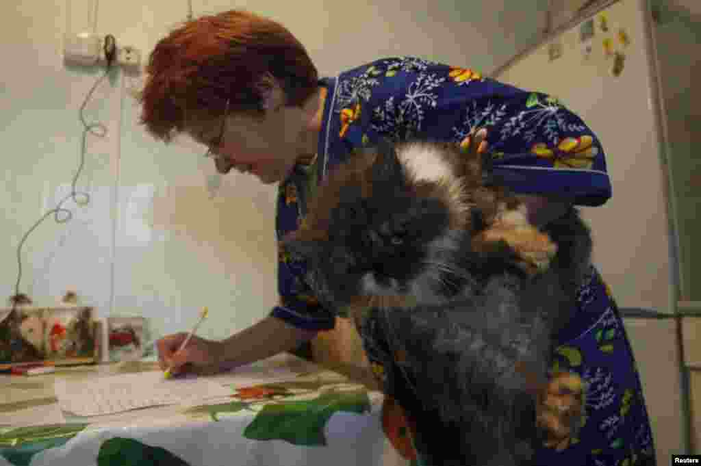 A woman holds her cat as she signs a form before casting her vote into a portable ballot box inside her house in the village of Slobodschina.
