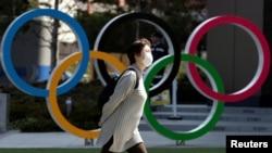 Женщина в маске проходит в Токио рядом с инсталляцией в форме олимпийских колец.
