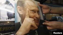 An employee holds an album containing a selection of photos of presidential candidate and current Prime Minister Vladimir Putin, which costs about 1,300 rubles ($45) each, at a bookstore in St. Petersburg on March 2.