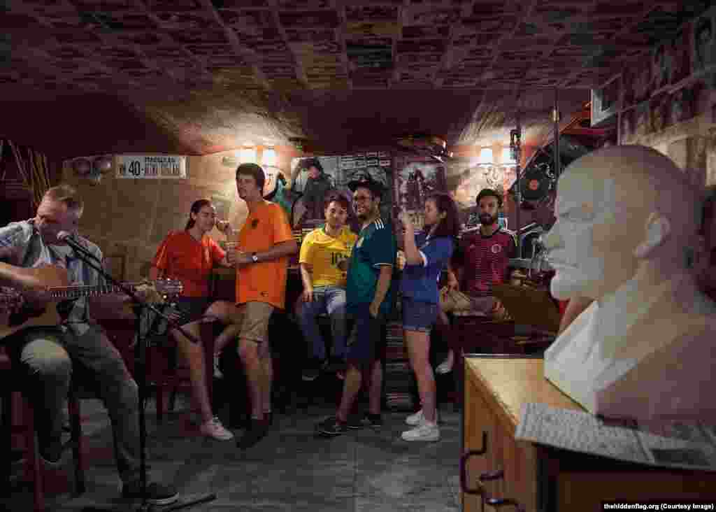 "The group in a bar next to a bust of Lenin. Brazilian Eloi Pierozan Junior (in yellow) says his boyfriend warned him of the danger of protesting gay rights in Russia, but says ""I'm not worried about the risk, it's a project that I really want to be involved in.... It's a call to love."""
