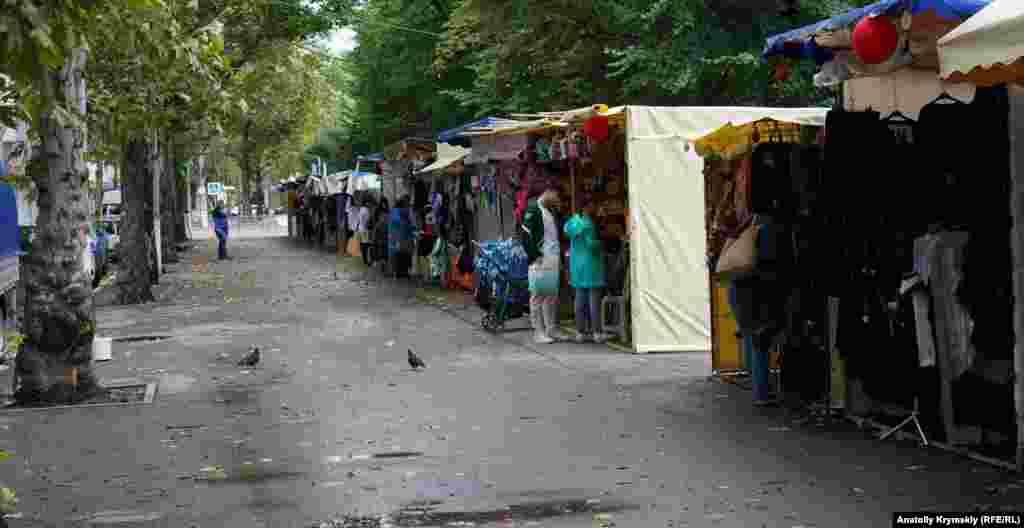 Одиночные покупатели на школьном базаре на краю парка Тренева