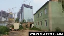 Один из домов Курмановых, который местные власти не легализовали. Сзади дома стройка комплекса «Абу-Даби Плаза». Астана, 26 июля 2016 года.