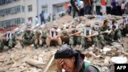 Žena plače nad ruševinama među kojima spasilačke ekipe traže preživele, 11 avgust 2010