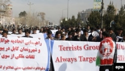 Afghan people hold banners during an anti-Taliban protest in Kabul on February 17.
