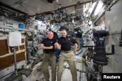 НАСАнын астронавты Скотт Келли (солдо) жана орус космонавты Михаил Корниенко Эл аралык орбиталдык станцияда. 21-январь 2016.